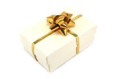 Cream Gift Box with Gold Ribbon. Textured cream giftbox with gold ribbon and bow royalty free stock photo