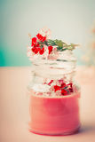 Cream in glass jar for skin care with flowers at turquoise background, front view. Beauty, natural cosmetic stock image
