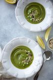 Green pea soup in vintage plate on concrete background. Flay lay. Cream of green pea soup with served with seeds, fresh pea and lemon. Healthy vegan food. View stock photography