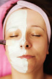 Cream half face. Spa and beauty salon, woman with half face covered with cream royalty free stock photography