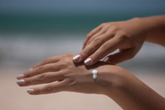 Cream on hand at the beach Royalty Free Stock Images