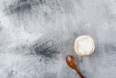 Cream ice cream in a waffle cup and a spoon. Vanilla cream ice cream in a waffle cup and a wooden spoon on a gray background. Top view. Copy space Royalty Free Stock Images