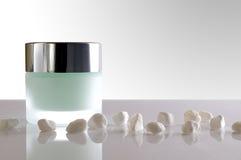 Cream jar closed and small white stones  Stock Photo