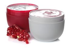 Cream in a jar next to fresh pomegranate on a white isolated background stock photos