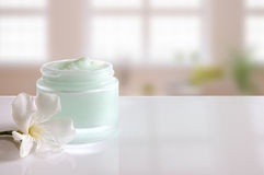 Cream jar open with flower front view windows background Stock Photos