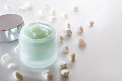 Cream jar open and small white stones  Royalty Free Stock Photography