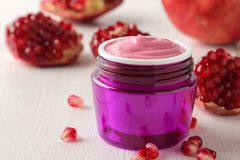 Cream in a lilac jar and with fresh pomegranate on a white wooden table. pomegranate extract. cosmetics. Cosmetic cream in a lilac jar and with fresh royalty free stock image
