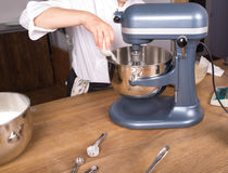 Cream mixing on kitchen table with kitchenware Stock Images