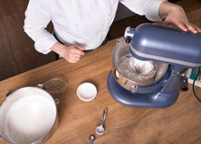 Cream mixing on kitchen table with kitchenware Stock Photography