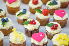 Cream Muffins with berries. Delicious cream cakes decorated with berries and cute figurines royalty free stock photo