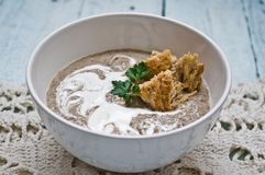 Cream of mushroom soup. Bowl with cream of mushroom soup on a wooden table stock photo