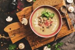 Cream of mushroom soup on a cutting board, rustic background. Winter warming hot soup. Top view, flat lay