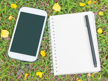 Cream notebook with pen and mobile phone Stock Photos
