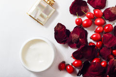 Cream, petals of rose and rose hips Stock Images