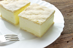 Cream pie with layers of puff pastry in plate. On wooden table Stock Photo