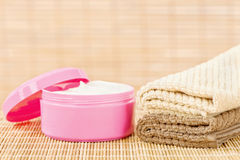 Cream in pink cup with towels Royalty Free Stock Photography