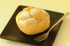 Cream puff. And fork on the plate Royalty Free Stock Photos