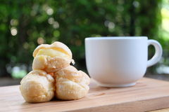 Cream puff with a cup of tea in the garden. Cream puff on wood tray with a cup of tea in the garden Royalty Free Stock Images
