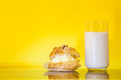 Cream puff and milk. Cream puff and a glass of milk in yellow background royalty free stock image