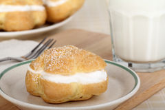 Cream Puff and Milk. Cream puff on a plate with a glass of milk royalty free stock photo
