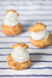 Cream Puff Pastry. Three Cream Puff Pastry on Tablecloth Royalty Free Stock Images