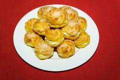 Cream puff pile on white plate Stock Photo