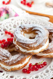 Cream puff rings decorated with fresh red currant Stock Image