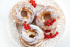 Cream puff rings decorated with fresh red currant Royalty Free Stock Images