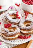 Cream puff rings decorated with fresh red currant Royalty Free Stock Photography