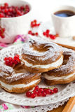 Cream puff rings decorated with fresh red currant Royalty Free Stock Photos
