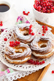Cream puff rings decorated with fresh red currant Stock Photography