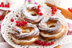 Cream puff rings decorated with fresh red currant Royalty Free Stock Photo