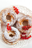 Cream puff rings decorated with fresh red currant Stock Images