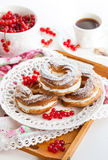 Cream puff rings decorated with fresh red currant Stock Photos