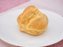 Cream puff on white dish, on pink tablecloth Royalty Free Stock Image