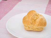 Cream puff on white dish, on pink tablecloth Royalty Free Stock Photo