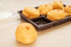 Cream puffs and plastic box Royalty Free Stock Photo