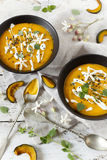 Cream of pumpkin and carrot soup on two black japanese bowls with sour cream Royalty Free Stock Photos