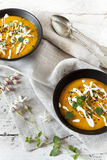 Cream of pumpkin and carrot soup on two black japanese bowls with sour cream Royalty Free Stock Images