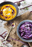 Cream of pumpkin and purple carrot soup on two  japanese bowls with sour cream and black sesame seed Stock Images