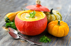 Cream pumpkin soup in a pumpkin. Soup in a pumpkin with different pumpkins and spoons Royalty Free Stock Photography