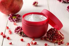 Cream in a red jar with flowers and fresh pomegranate on a white wooden table. pomegranate extract. cosmetics. Cosmetic cream in a red jar with flowers and royalty free stock image