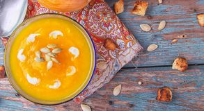 Cream of roasted pumpkin spicy soup traditional simple vegetarian autumn vegetable healthy organic diet homemade food meal on. Vintage wooden table background royalty free stock images