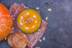 Cream of roasted pumpkin spicy soup traditional simple vegetarian autumn vegetable healthy organic diet homemade food meal on. Black background royalty free stock photo