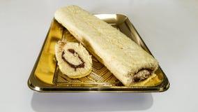 Cream roll. Chocolate - hazelnut cream roll on a gold tray Stock Image