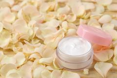 Cream in rose petals. Cosmetics for face and body in pink bottles with fresh roses. spa. place for text stock photo