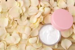 Cream in rose petals. Cosmetics for face and body in pink bottles with fresh roses. spa. place for text. top view royalty free stock photography