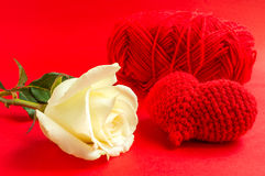 Cream rose with red heart crochet on red background Stock Image