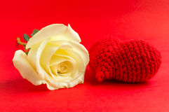 Cream rose with red heart crochet on red background Royalty Free Stock Images