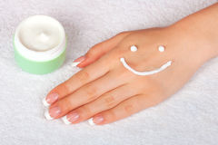 Cream smile face on female hand Royalty Free Stock Photo